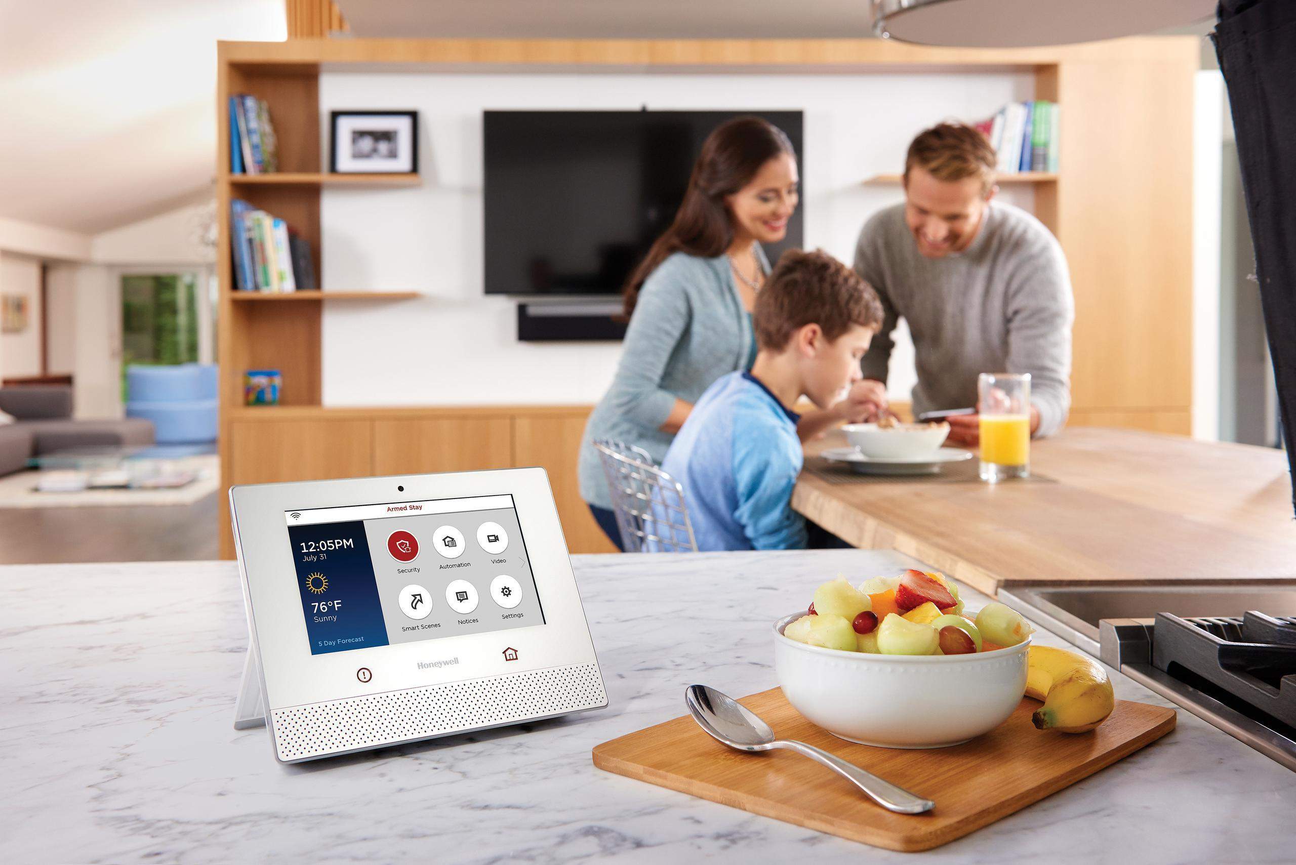 Family eating breakfast with a smart home automation console nearby